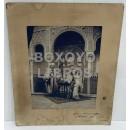 Fotografía de escena de maurofilia o 'a la morisca' de dos caballeros ataviados con decorado de la Alhambra con el Patio de los Leones de fondo en 1912